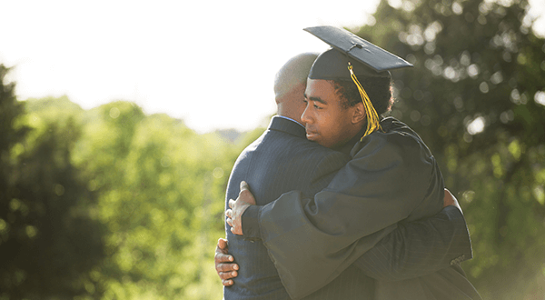 Son in a graduation gown hugging his father stock photo